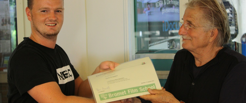 Geslaagd voor de Zomercursus Reportagemaken niveau 1. Derk Gruppen ontvangt zijn getuigschrift uit handen van Frans Bromet.